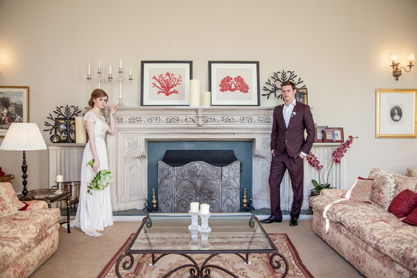 Bride and groom standing by fireplace