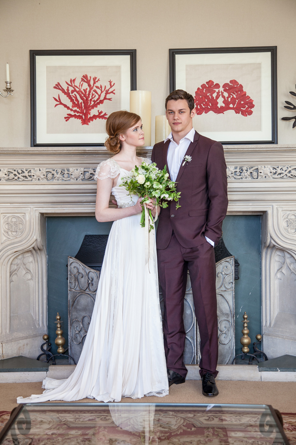 Bride and groom standing in front of fireplace