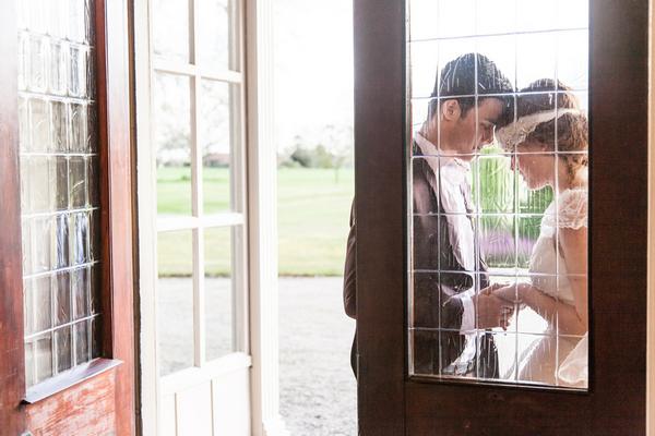Bride and groom standing by door