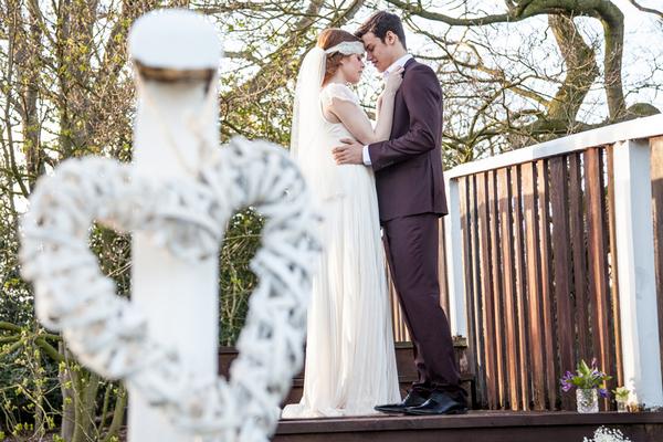 Bride and groom standing on wooden bridge