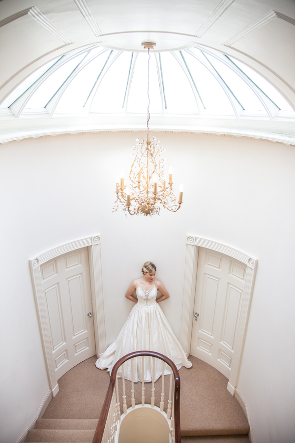 Bride standing at top of stairs in Ormesby Manor