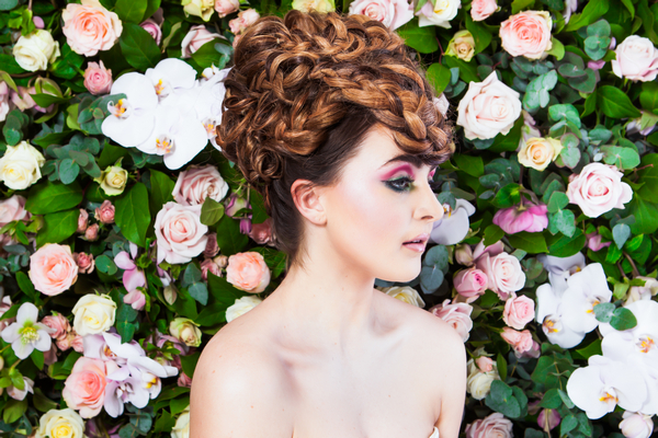 Bride with updo in front of flower wall