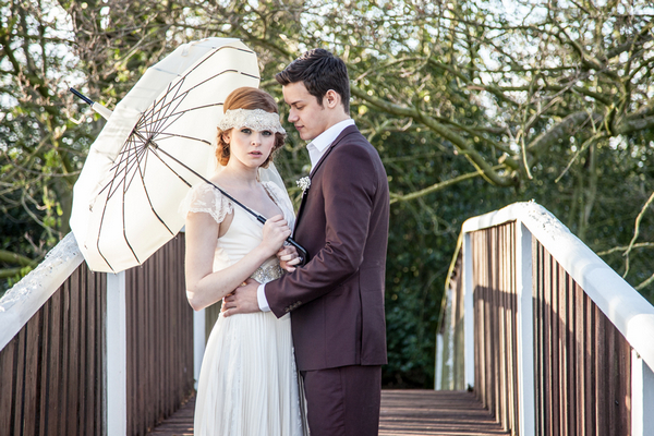 Bride and groom holding parasol