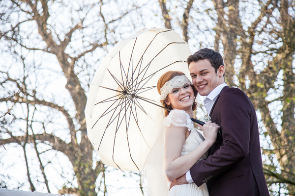 Bride and groom holding parasol and smiling