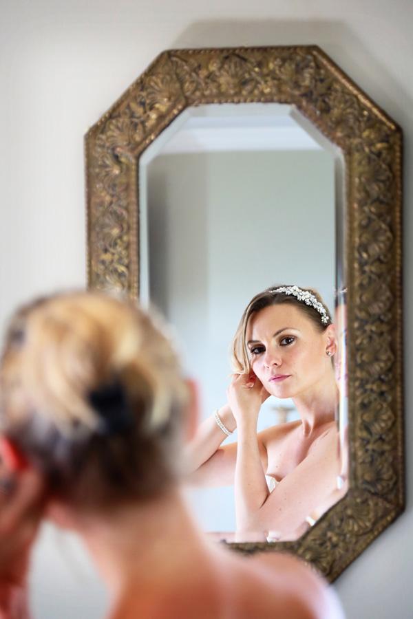 Bride putting earring on looking in mirror