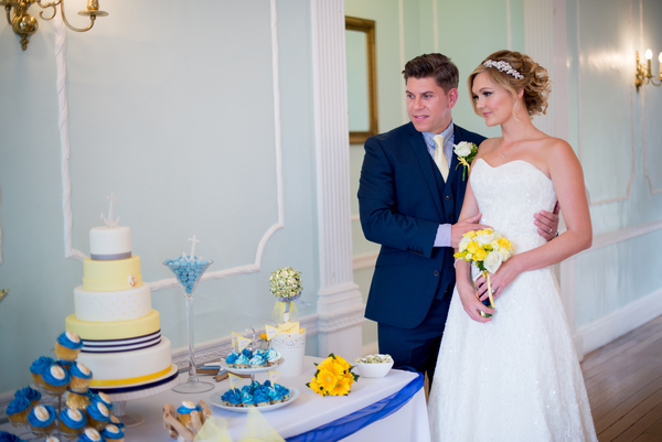 Bride and groom looking at cake table