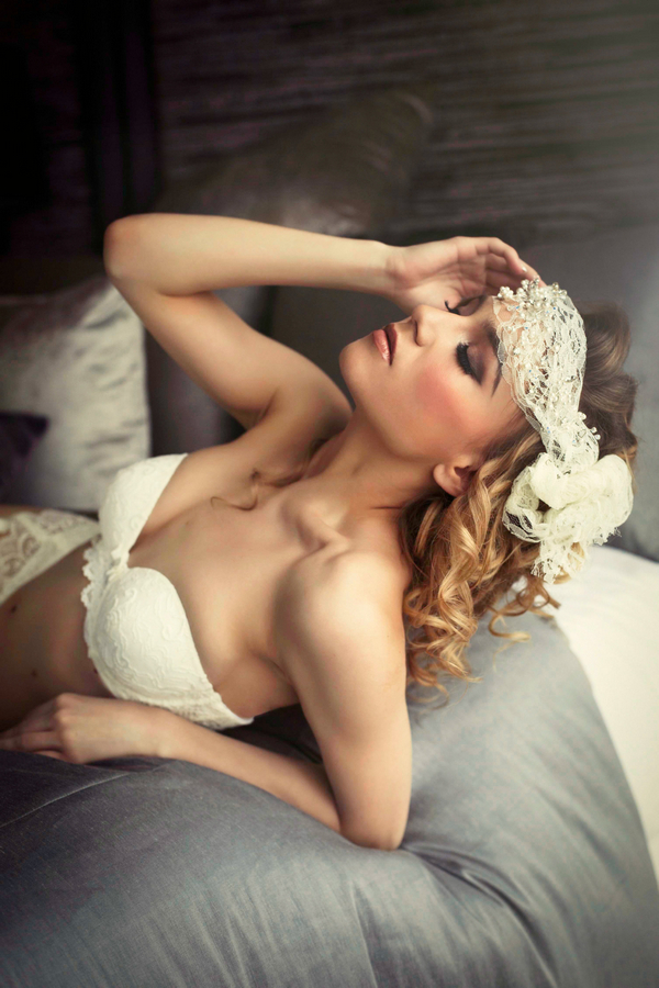 Woman with lace headband leaning back on bed - Bridal boudoir shoot