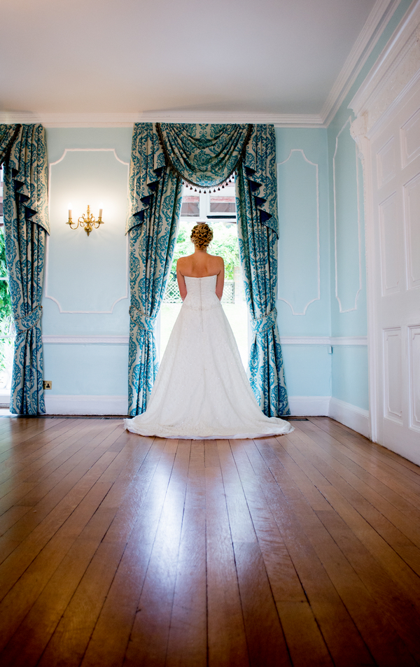 Bride standing at window