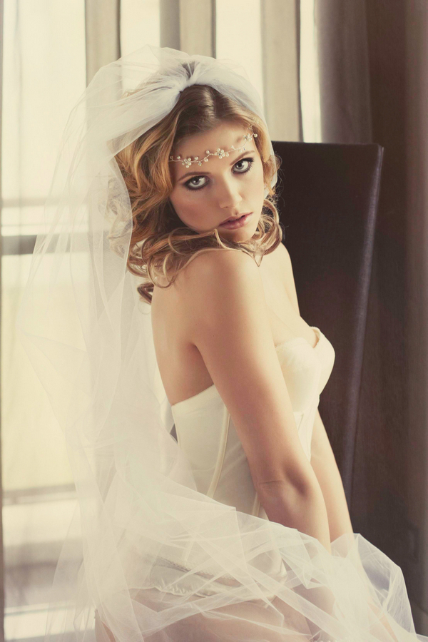 Woman with corset and bridal veil sitting on bed - Bridal boudoir shoot
