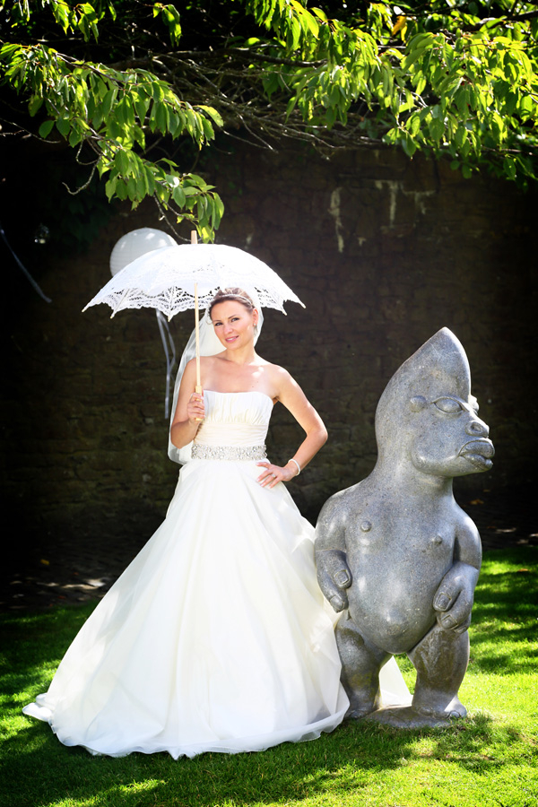 Bride with parasol standing next to statue in Walton Castle grounds