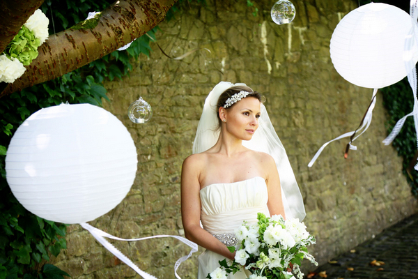 Bride holding bouquet next to balloons