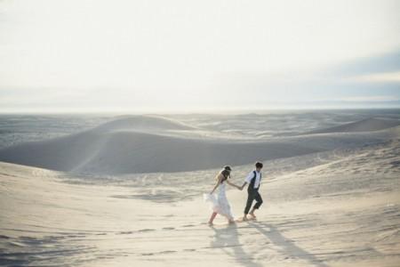 Bride and groom walking across desert