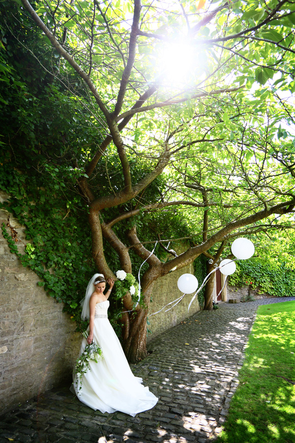 Bride next to wishing tree in Walton Castle garden