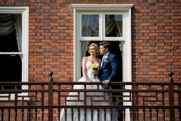 Bride and groom standing on balcony