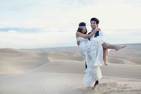 Groom carrying bride across desert