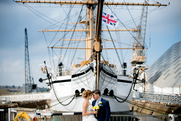 Bride and groom standing in front of boat at The Dockyard Chatham