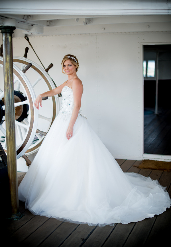 Bride standing at ship's wheel