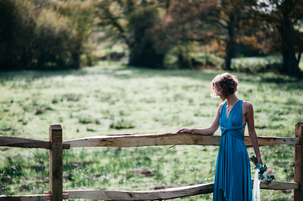 Bridesmaid standing next to fence