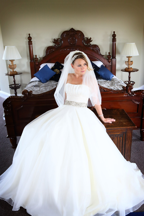 Bride sitting on chest at end of bed