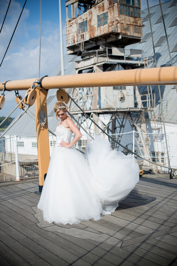 Bride on ship deck with dress blowing in wind