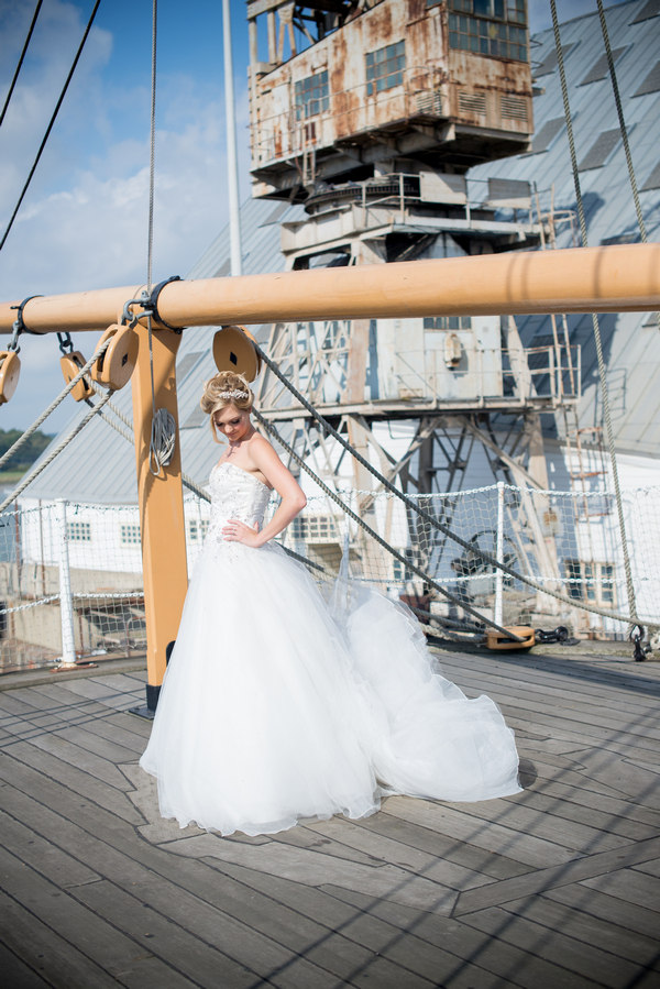 Bride on ship deck with dress dropping to ground