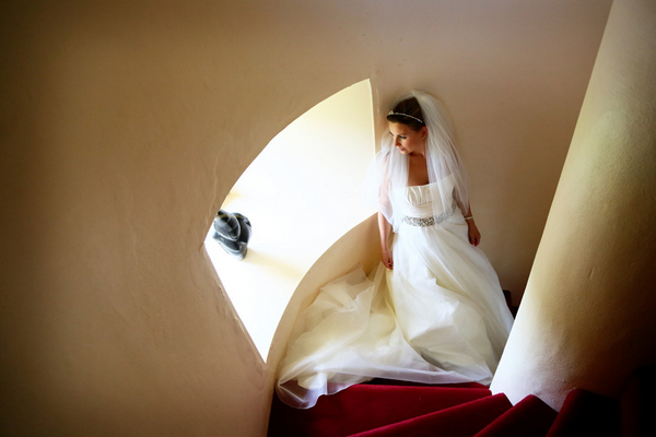 Bride standing on spiral staircase looking out of window