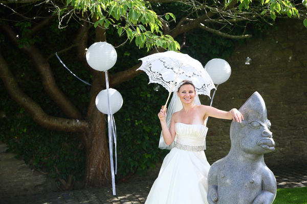 Bride holding parasol leaning on statue