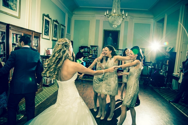 Bride and bridesmaids dancing in Library at The In and Out