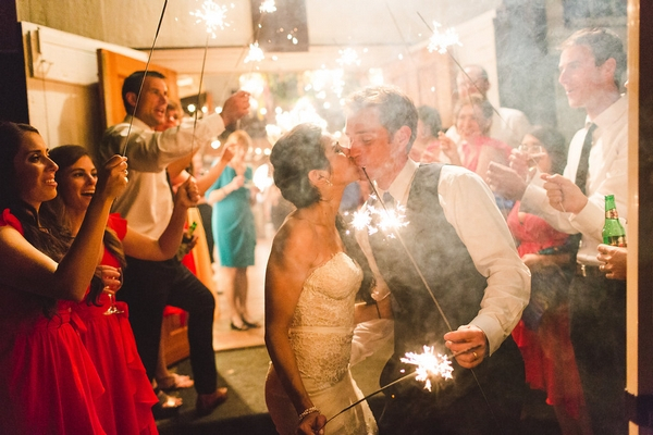 Bride and groom kiss holding sparklers