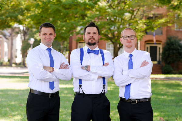 Groomsmen with blue ties and arms folded