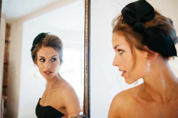 Bridesmaid with hair bow looking in mirror