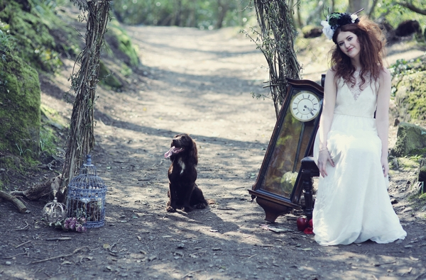 Bride sitting with dog in woods