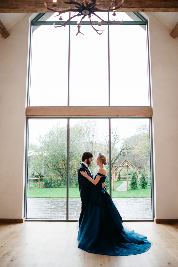 Bride and groom standing by large window