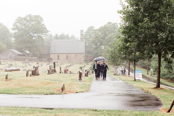 Guests walking to wedding in rain