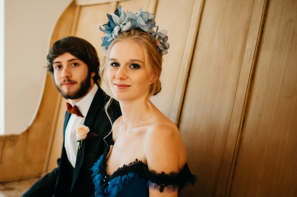 Bride with blue wedding dress and blue hairpiece sitting next to groom