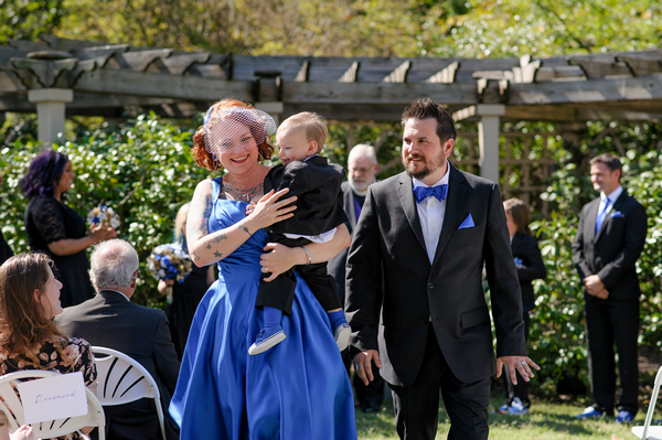 Bride in blue dress carrying young boy