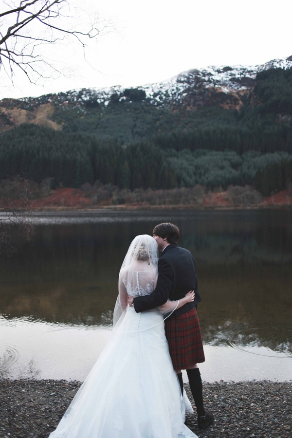 Bride and groom looking at loch