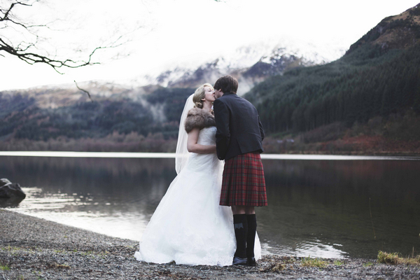 Bride and groom kissing by loch