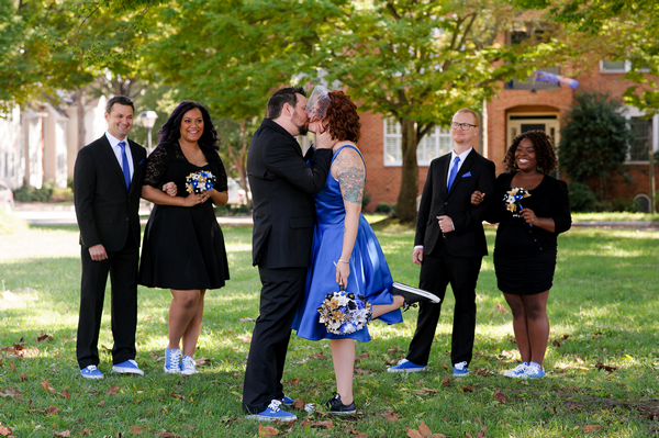 Bride and groom kiss as bridal party watch