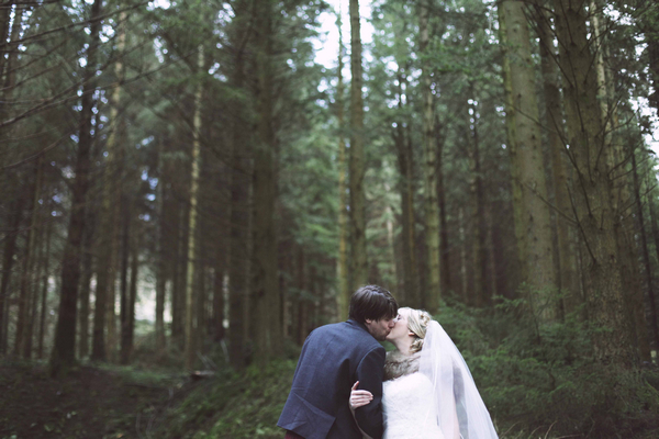 Bride and groom kissing in woodlands
