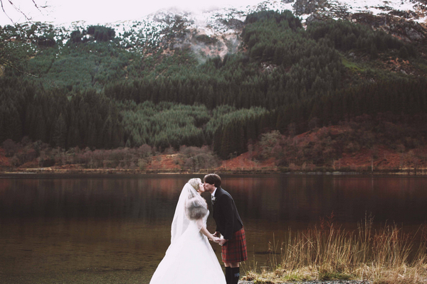 Bride and groom kissing in front of loch