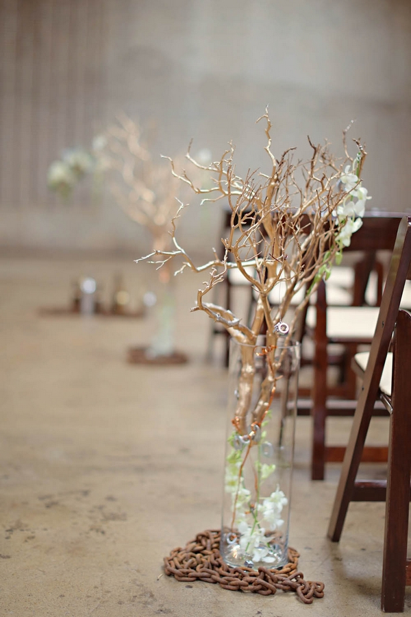 Branches in vases as aisle decoration