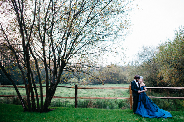 Bride and groom next to fence in field