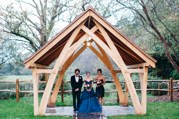 Bride, groom and bridesmaid under wooden frame