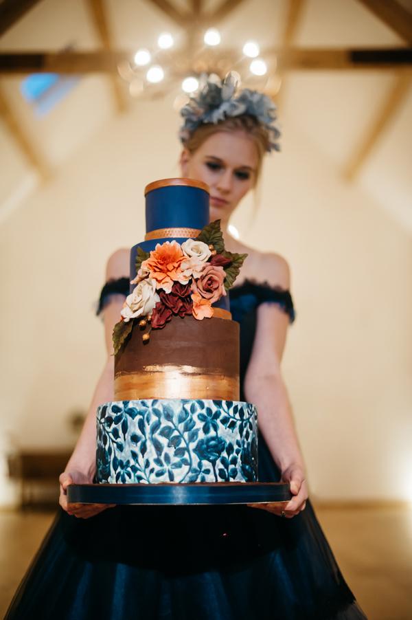 Bride holding blue and gold wedding cake