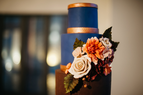 Flowers on blue and gold wedding cake