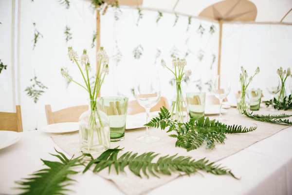 Leaf and bottles of flowers on wedding table