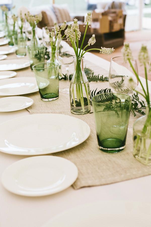 Green glasses and hessian runner on wedding table