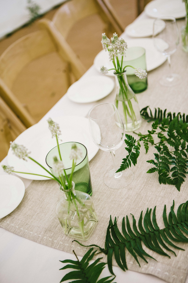 Green glass and bottle of flowers on wedding table