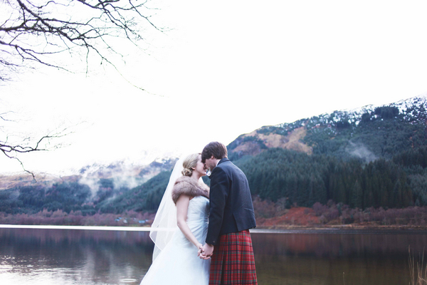 Bride and groom in front of loch and mountains in Scotland